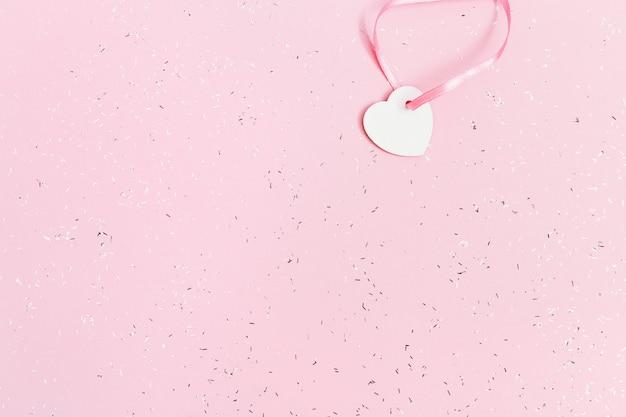 Białe serduszko na różowym papierze pokrytym cekinami