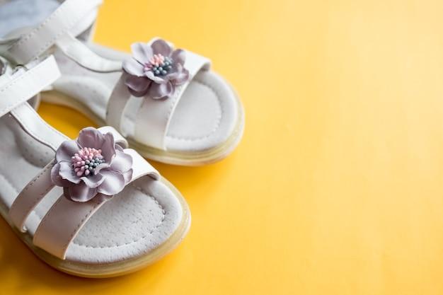 Białe skórzane sandały dla dziewczynki z kwiatową dekoracją
