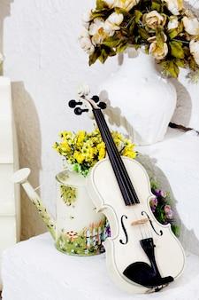Białe skrzypce z kwiatami i białym pokoju