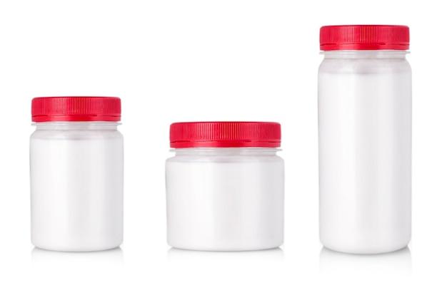 Białe słoiki z czerwoną nakrętką bez etykiety
