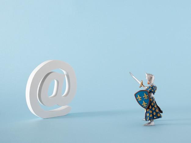 Białe słowo na dla wiadomości e-mail i internetowych oraz zabawka-wojownik na pastelowym niebieskim tle. sztuka abstrakcyjna. nowoczesny pomysł na wirtualną twórczą dekorację.
