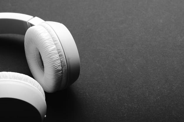 Białe słuchawki bezprzewodowe nauszne na czarnym stole. close-up, kopia przestrzeń.