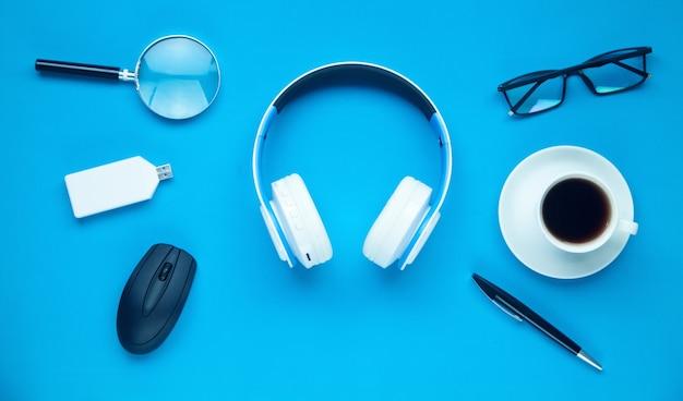 Białe słuchawki bezprzewodowe, okulary, kawa i inne przedmioty na niebiesko