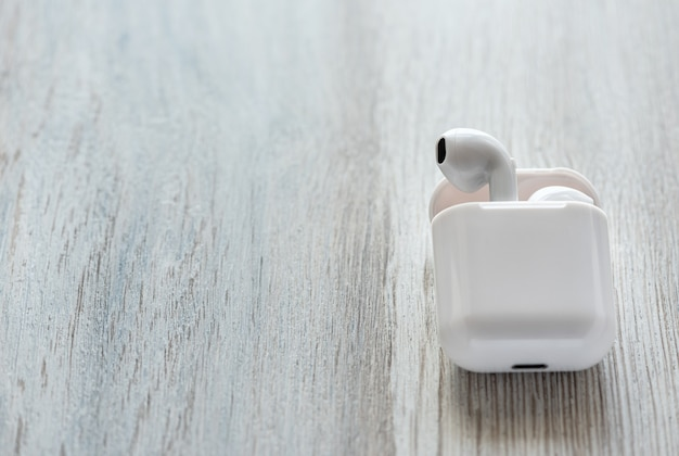 Białe słuchawki bezprzewodowe w etui ładującym na drewnianym tle.