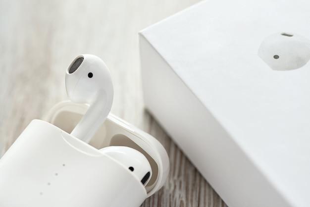 Białe słuchawki bezprzewodowe w etui ładującym