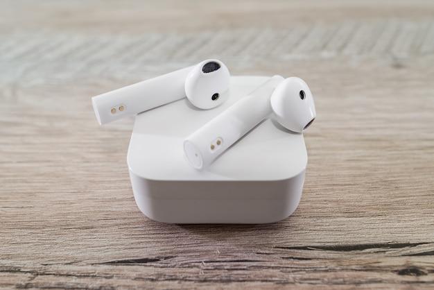 Białe słuchawki bezprzewodowe w pudełku na drewnianym stole