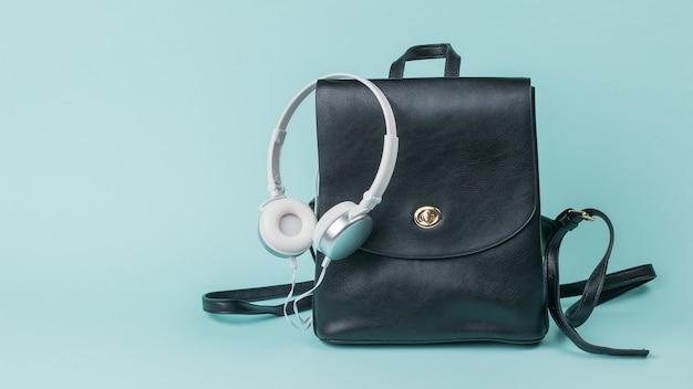 Białe słuchawki i czarny skórzany plecak na niebiesko