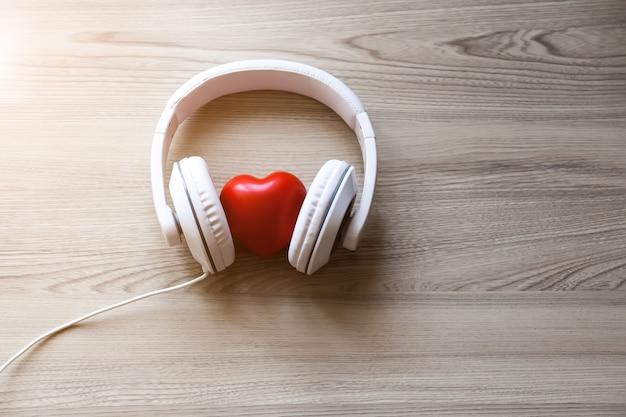 Białe słuchawki i czerwone serce na środku