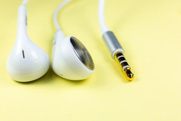 Białe słuchawki leżące na żółtym tle. koncepcja muzyki współczesnej. technologia audio. zamknij się zdjęcie.