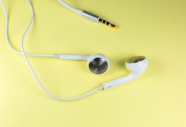 Białe słuchawki leżące na żółtym tle. koncepcja nowoczesnej muzyki. technologia audio. zamknij zdjęcie.