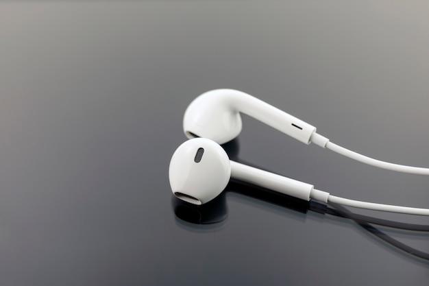 Białe słuchawki na czarnym tle