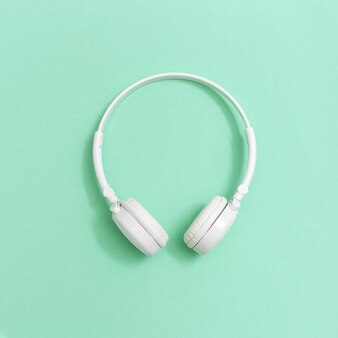 Białe słuchawki na tle papieru. koncepcja festiwali muzycznych, stacji radiowych, melomanów. minimalistyczny styl. kartka z życzeniami.