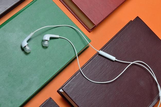 Białe słuchawki próżniowe leżą na książkach ułożonych na pomarańczowym tle. koncepcja audiobooka.