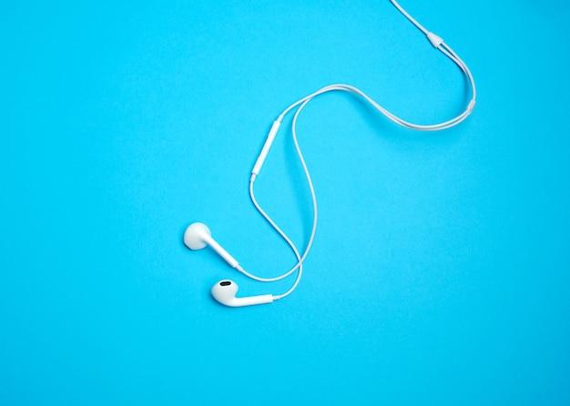 Białe słuchawki z kablem na niebieskim tle