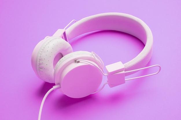 Białe słuchawki z przewodem na pustym fioletowym tle