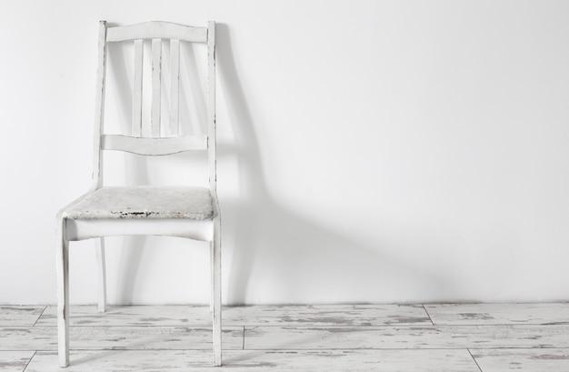 Białe stare drewniane krzesło w białym wnętrzu vintage