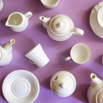 Białe stylowe minimalistyczne dania na kawę i herbatę na fioletowym jasnym tle. koncepcja zastawy stołowej. widok z góry