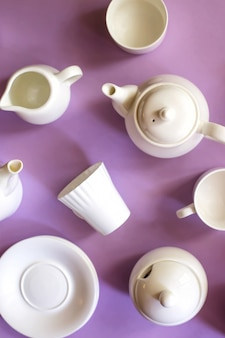 Białe stylowe minimalistyczne dania na kawę i herbatę na fioletowym jasnym tle