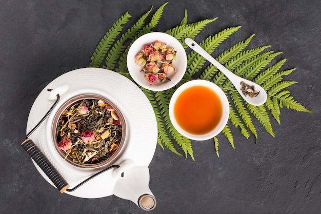 Białe suche kwiaty i liście do herbaty ziołowej z liśćmi paproci na czarnej powierzchni