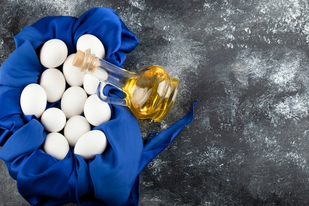 Białe surowe jaja kurze w szklanej butelce oleju.