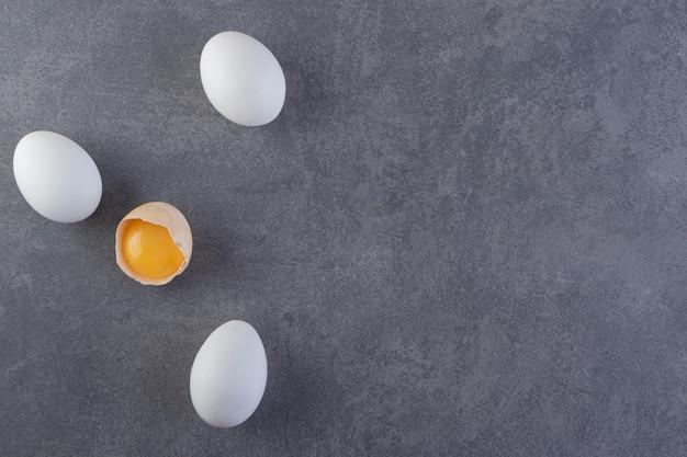 Białe surowe jajka i popękane jajko umieszczone na kamiennym stole.