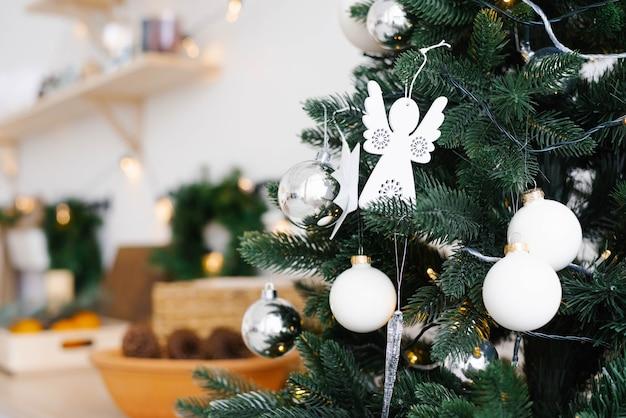 Białe świąteczne zabawki na zbliżeniu choinki