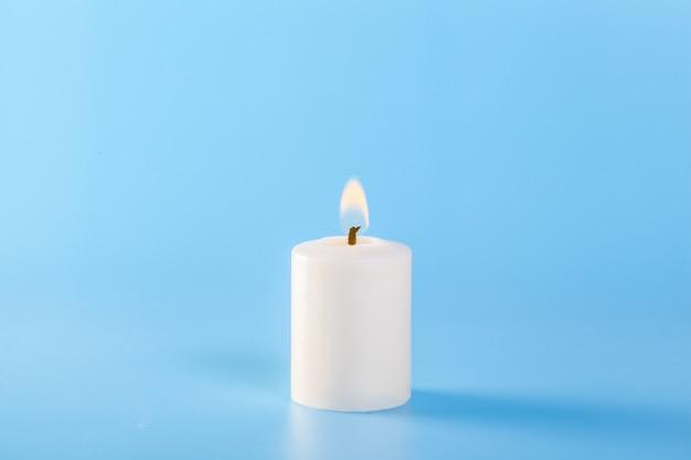Białe świeczki na błękitnej ścianie