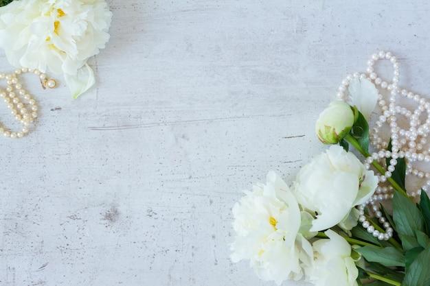 Białe świeże kwiaty piwonii z biżuterią z pereł na białej drewnianej ramie
