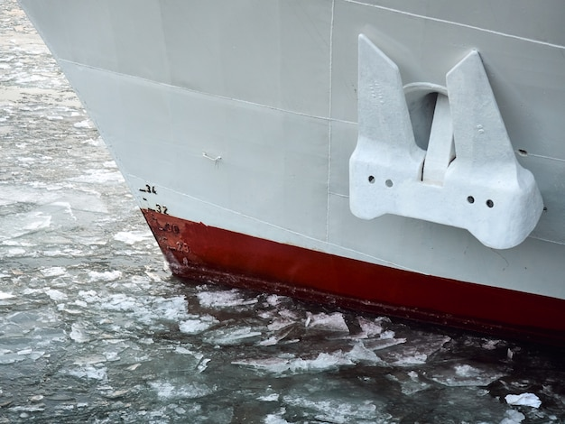 Białe, szare, czerwone zbliżenie dziobu statku zimą w lodowym morzu rzeki, linia wodna zanurzona w łamanym lodzie.