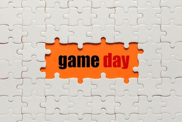 Białe szczegóły układanki na dzień gry w kolorze pomarańczowym i słownym.