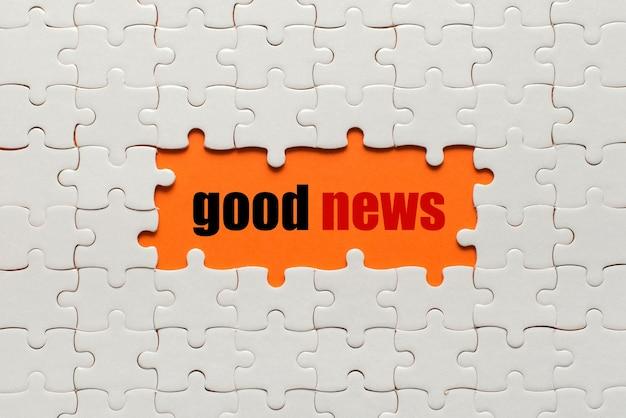 Białe szczegóły układanki na pomarańczowo i słowo dobra wiadomość.