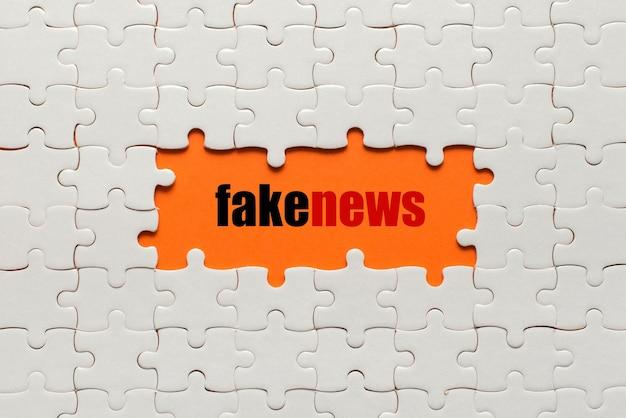 Białe szczegóły układanki na pomarańczowych i słownych fałszywych wiadomościach