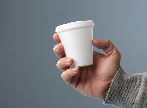 Białe szkło termiczne z pokrywką w ręku na szarym tle