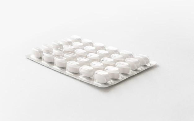 Białe tabletki leku w opakowaniu