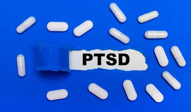 Białe tabletki leżą na pięknym niebieskim tle. w środku biały papier z napisem ptsd.