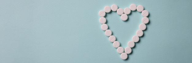 Białe tabletki leżące w kształcie serca na niebiesko