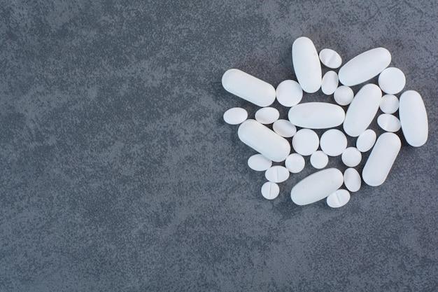 Białe tabletki medyczne na powierzchni marmuru