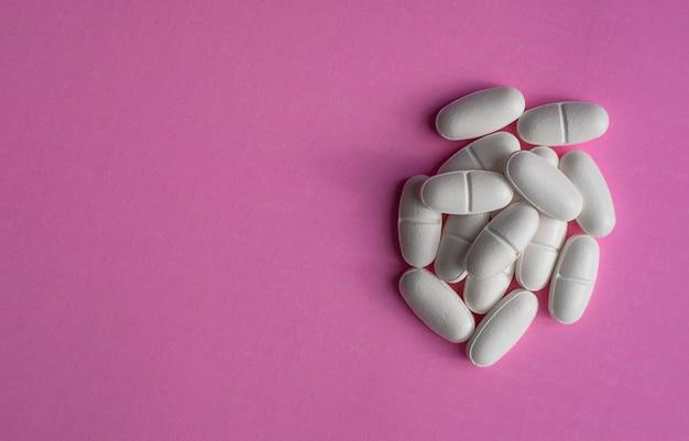 Białe tabletki na fioletowym tle