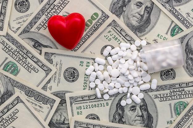 Białe tabletki są rozrzucone po dolarach i sercu