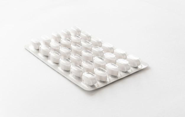 Białe tabletki w blistrze na stole