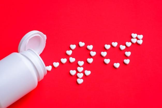 Białe tabletki w kształcie serca dają znaki mężczyzny i kobiety na czerwonym tle