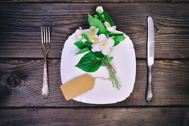 Białe talerze i metalowe sztućce