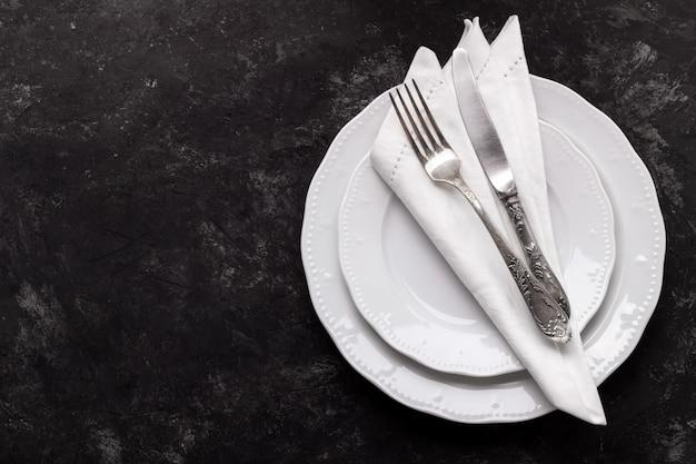 Białe talerze i zabytkowe sztućce