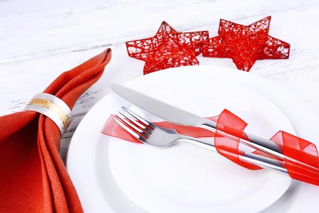 Białe talerze, nóż, widelec, serwetka i świąteczne dekoracje na drewnianym tle