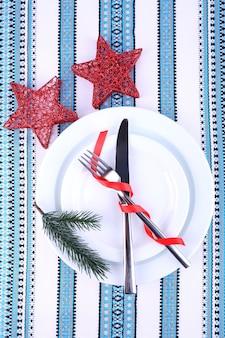 Białe talerze, nóż, widelec, serwetka i świąteczne dekoracje na obrusie