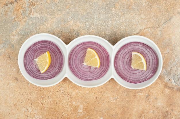 Białe talerze pełne pokrojonej w plasterki cebuli i cytryny