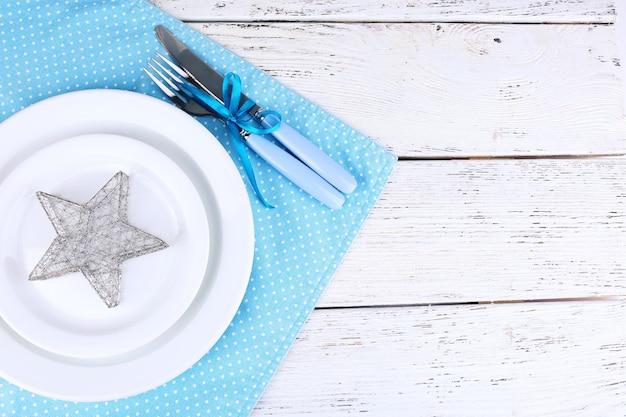 Białe talerze, widelec, nóż i świąteczne dekoracje na niebieskiej serwetce w kropki na drewnianej powierzchni