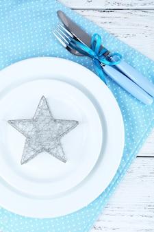 Białe talerze, widelec, nóż i świąteczne dekoracje na niebieskiej serwetce w kropki na drewnianym tle