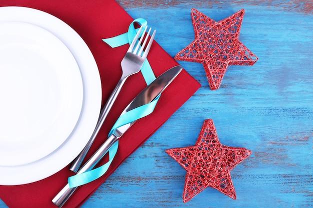 Białe talerze, widelec, nóż i świąteczne dekoracje na serwetce na drewnianym tle