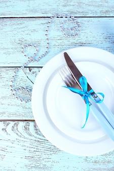 Białe talerze, widelec, nóż, serwetka i świąteczne dekoracje na drewnianym tle